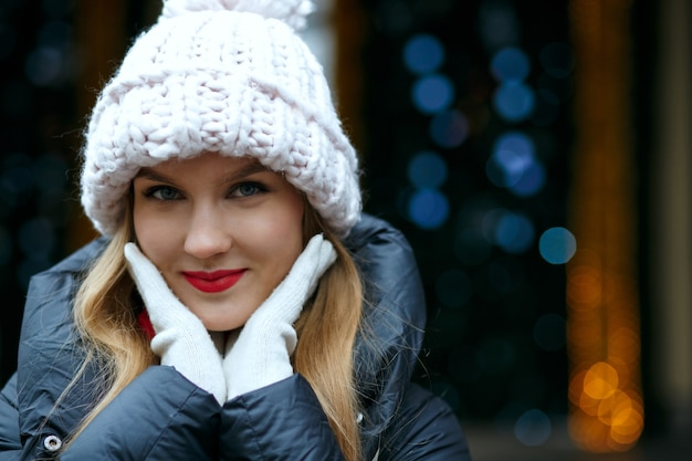 ボケと花輪の背景の上で通りでポーズをとってニット帽をかぶった赤い唇を持つ楽しいブロンドの女性