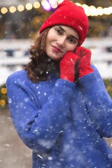 降雪時にクリスマスフェアで歩く楽しいブルネットの女性
