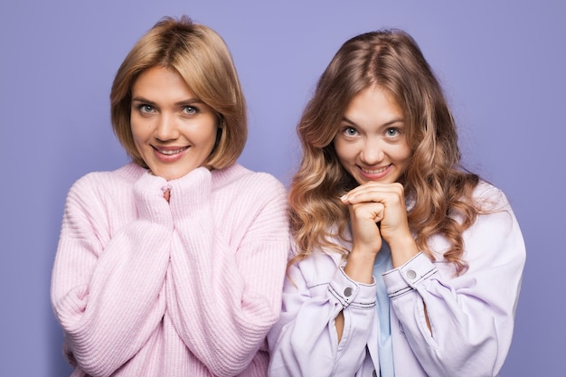 Delightful caucasian blonde women in warm sweater is smiling touching the chin with fist on violet  wall