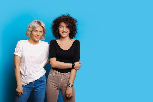 곱슬 머리를 가진 유쾌한 백인 여성은 여유 공간이있는 파란색 벽에 무언가를 홍보하고 있습니다.
