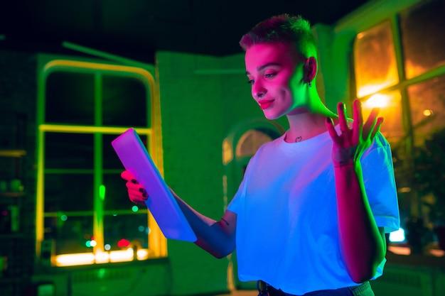 매우 기쁜. 네온 조명 인테리어에 세련 된 여자의 영화 초상화. 영화 효과와 같은 톤, 밝은 네온 색상. 실내 화려한 불빛에 태블릿을 사용 하여 백인 모델. 청소년 문화.