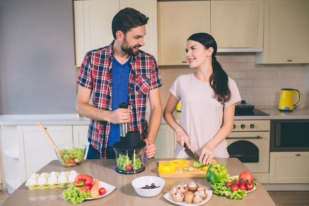 Delightful couple works together. girl is cutting cucumber into pieces and looks at guy.