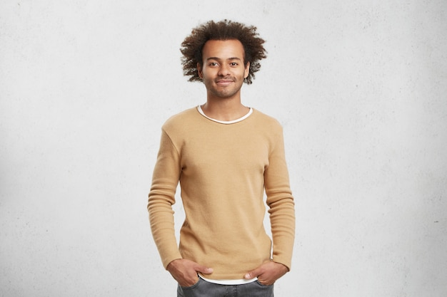 Delightful dark skinned man in sweater and jeans, look pleased at camera, has good mood as comes home after work