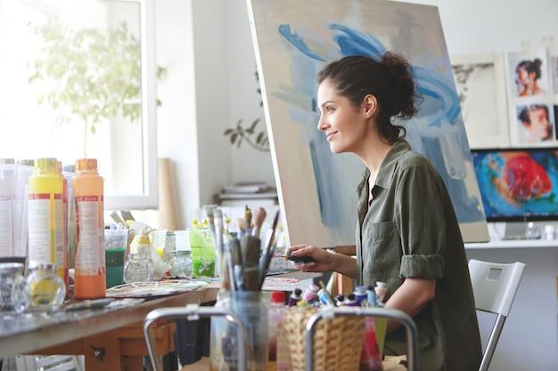 유쾌한 여성은 자연스럽게 옷을 입고 창을보고 그녀의 작업장에서 일하면서 햇살을 즐기고 아름다운 그림을 만들고 화려한 오일로 그림을 그립니다. 캔버스에 여자 화가