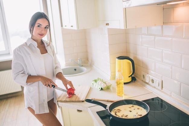 Восхитительная девушка режет помидор на кусочки. она готовит завтрак. есть яйца с грибами, жареные в сковороде на плите. она выглядит и улыбается.