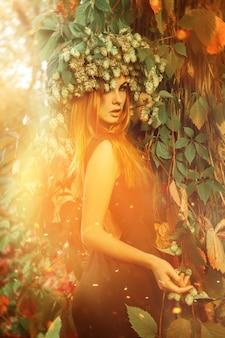 屋外の魔法の森でホップの花輪を持つ楽しい女性
