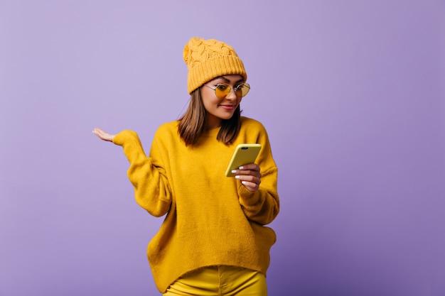 유럽에서 온 유쾌한 유쾌한 여학생이 놀람으로 그녀의 휴대 전화에서 sms를 찾고 있습니다. 노란색 따뜻한 모자와 고립 된 초상화를 위해 포즈를 취하는 화려한 안경 소녀