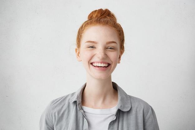 Восхитительная рыжая женщина с красивым веснушчатым лицом, небрежно одетая, улыбаясь