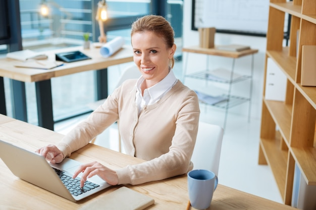 Delightful smile. charming office manager expressing pleasant emotions while sitting at the table and working with a laptop
