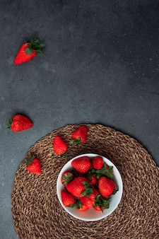 Delightful strawberries in a white bowl on a round placemat and grey grunge background. flat lay.