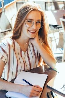 Восхитительный студент с рыжими волосами и веснушками делает заметки в очках и использует ноутбук в кафетерии