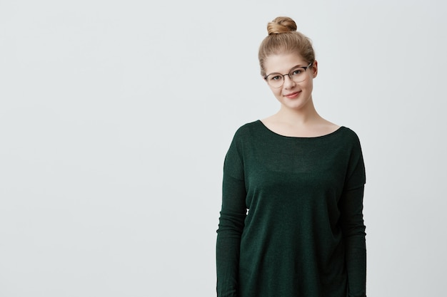 Delightful woman in stylish glasses, wears green loose sweater, stands indoors, smiles happily. caucasian girl with blonde hair in knot gently smiling . positive feelings and emotions.
