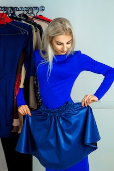 Delightful young blond woman trying on a skirt