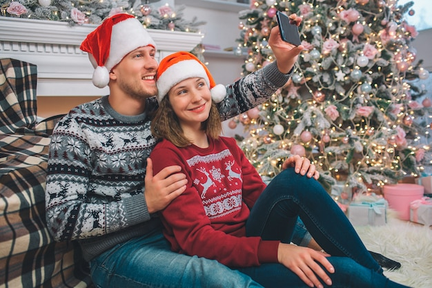 Delightful young couple sit together. they pose on camera. man holds phone in hands and take selfie. they smile. couple is in decorated room.