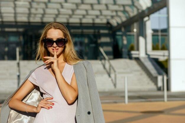 선글라스를 착용하고 침묵 제스처를 보여주는 유쾌한 젊은 여자. 텍스트를 위한 공간