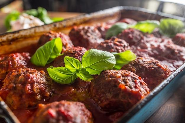 Вкусные итальянские мясные шарики из говядины с базиликом в старинной сковороде.