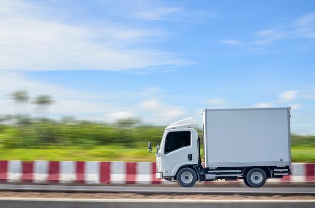 푸른 하늘을 배경으로 녹색 자연 경로를 따라 움직이는 작은 흰색 트럭을 배달합니다.