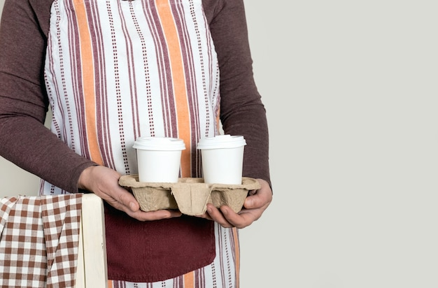 Deliver or barista holding container take away with two white cups of coffee.