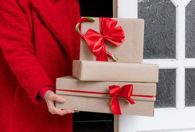 Доставка одетая в красное пальто, держа подарочные коробки возле белой двери в канун праздников рождества