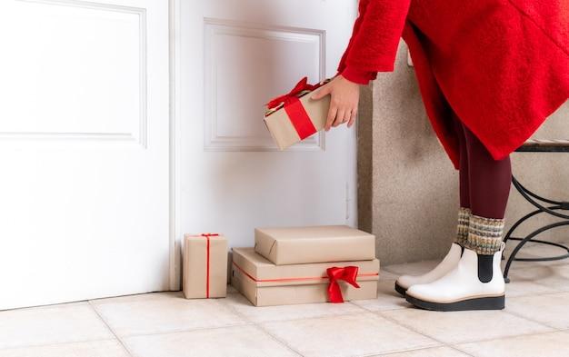 Доставить в красном пальто с подарочными коробками у белой двери накануне праздников.