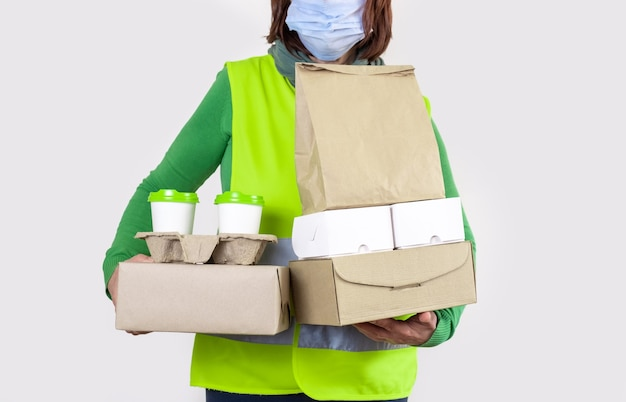 Deliver in a green vest holding paper boxes and container take away with two white cups of coffee.