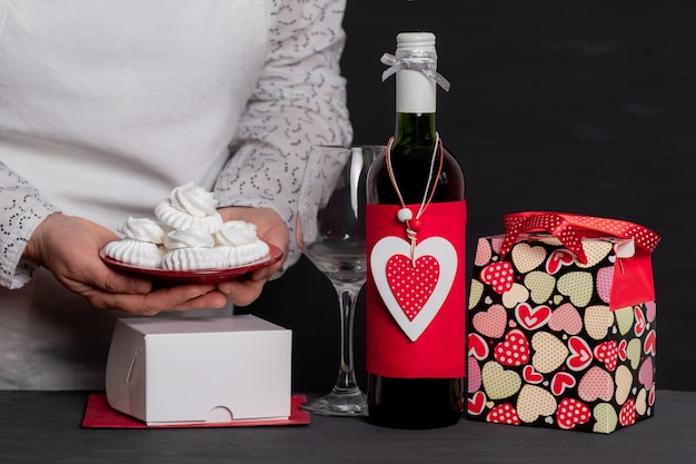 Deliver holding cakes near wine bottle with red heart of valentine's day and festive bag