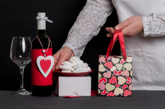 Deliver holding festive bag near wine bottle with red heart of valentine's day and cakes