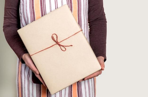 Доставка бумажной коробки с бордовой лентой на белом фоне.