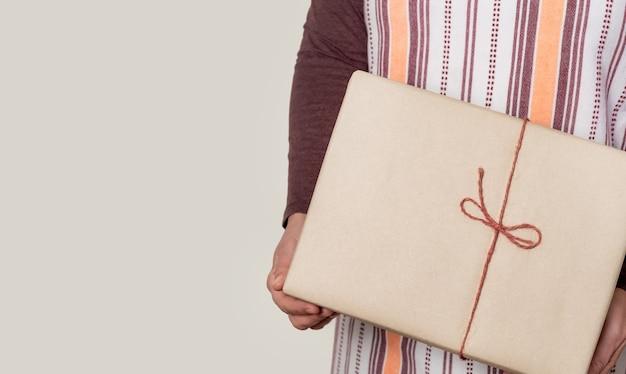 Доставьте бумажную коробку с бордовой лентой на белой стене.