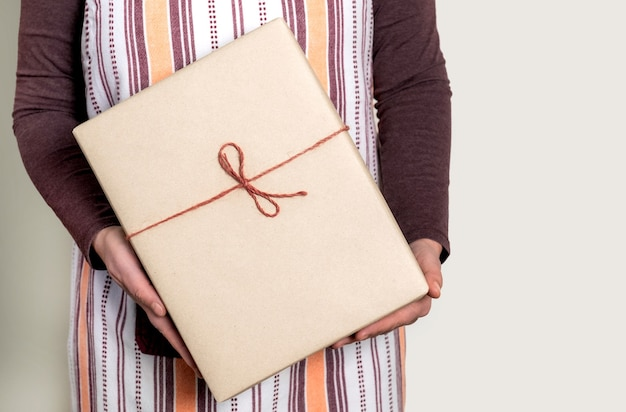 Deliver holding paper box with burgundy ribbon on the white background.