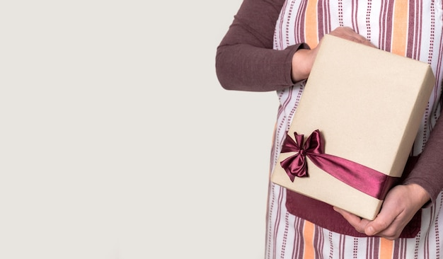 Deliver holding paper box with burgundy ribbon on the white surface.