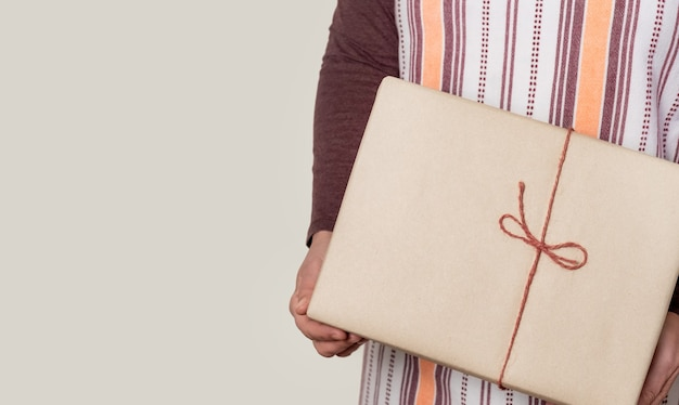 Deliver holding paper box with burgundy ribbon on the white wall.