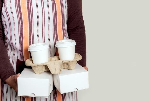 Доставьте бумажные коробки и возьмите контейнер с двумя белыми чашками кофе.