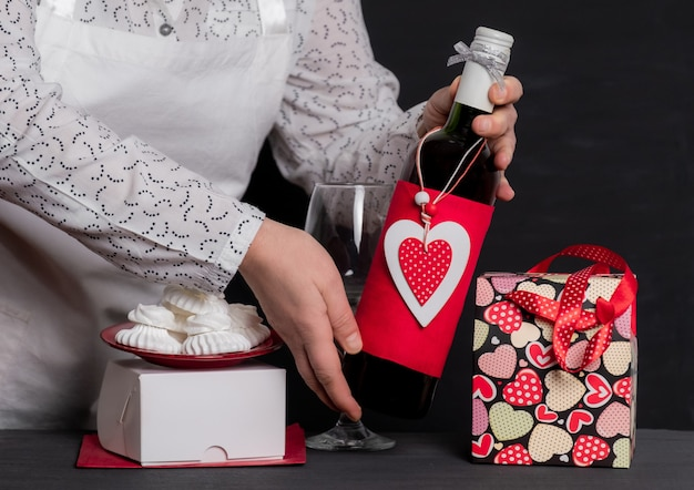 お祝いのバッグとケーキ用の白い箱の近くに赤いハートのバレンタインデーのワインボトルを持って配達する