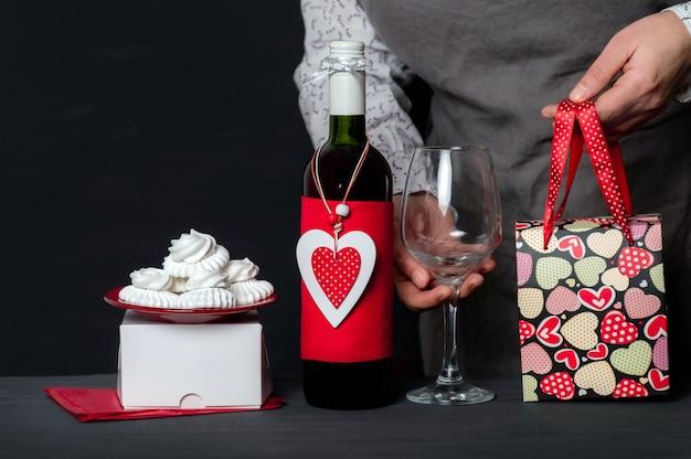 バレンタインデーの赤いハート、お祝いのバッグとケーキを備えたワインボトルの近くに保持ワイングラスをお届けします
