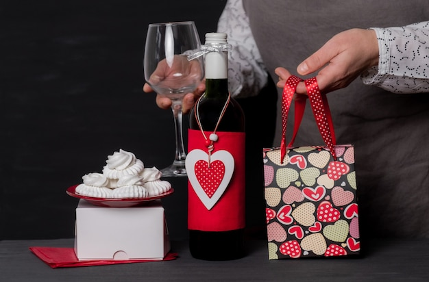 Deliver holding wineglass near wine bottle with red heart of valentine's day, festive bag and cakes