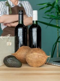 茶色のエプロンで配達ココナッツとアボカドの入った白い箱にワインボトルを入れます。オンライン注文のコンセプトです。