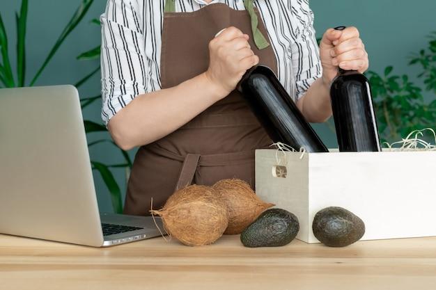 茶色のエプロンで配達ココナッツとアボカドの入った白いボックスにワインボトルを入れます。オンライン注文のコンセプトです。