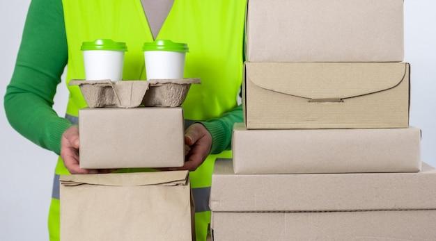 紙箱と容器を保持している緑色のベストで配達し、2杯の白いコーヒーを持ち帰ります。