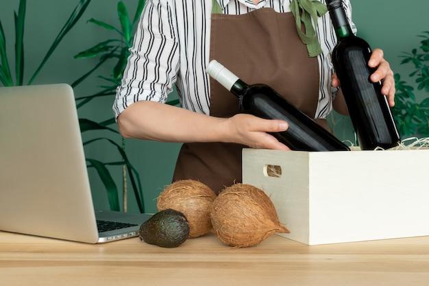 赤いエプロンで配達ココナッツとアボカドの入った白い箱にワインボトルを入れます。オンライン注文のコンセプトです。