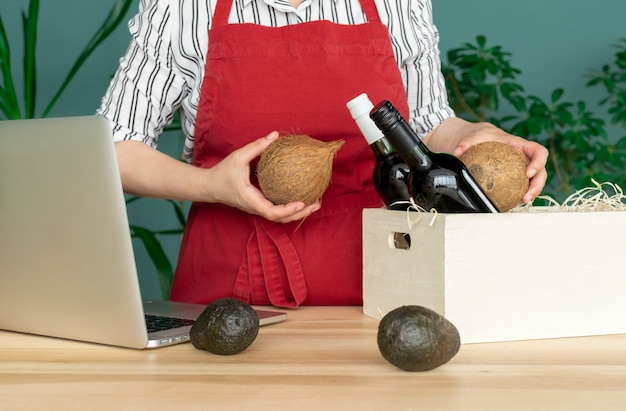 赤いエプロンで配達ココナッツとアボカド、オンライン注文のコンセプトでワインボトルを白いボックスに入れます。