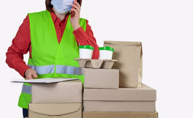 Deliver is in a green vest holding paper boxes and container take away with two white cups of coffee.
