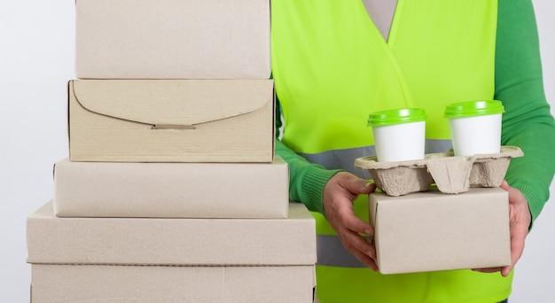 Доставщик в зеленом жилете с бумажными коробками и контейнер с двумя белыми чашками кофе.