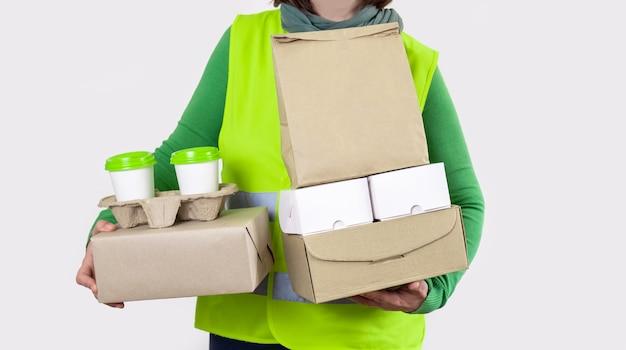 配達は紙箱を保持している緑のベストにあり、容器は2杯の白いコーヒーと一緒に持ち帰ります。