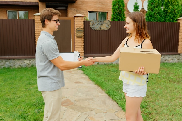 Deliver man and happy woman shaking hands each other after accepting a delivery package