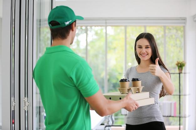 Доставить мужчину в зеленой униформе с сумкой с едой, подать чашку кофе женщине-костюмерше перед домом.
