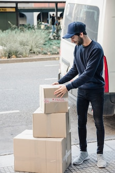 Deliver man looking at stacked cardboard boxes
