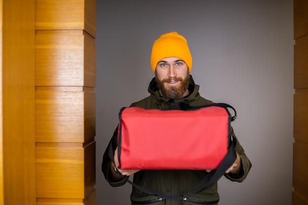 Consegnare a un uomo che indossa una maschera medica per il viso che maneggia la scatola di carta con la pizza all'interno, dare al cliente sulla porta