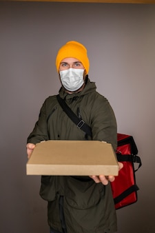 Deliver man wearing face medical mask handling paper box with pizza inside, give to costumer in doorway