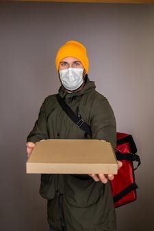 Доставить мужчину в медицинской маске для лица, обрабатывающего бумажную коробку с пиццей внутри, передать заказчику в дверном проеме